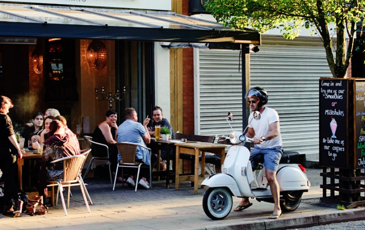 A man gets ready to leave a Didsbury bar on his white, trendy moped