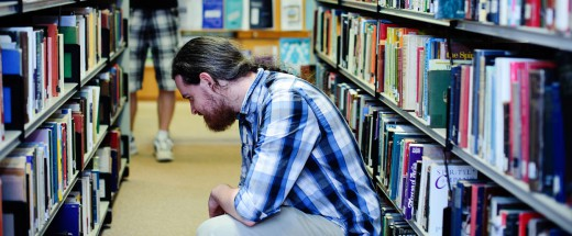 A student crouches to see the books on one of the lower shelves in the Library