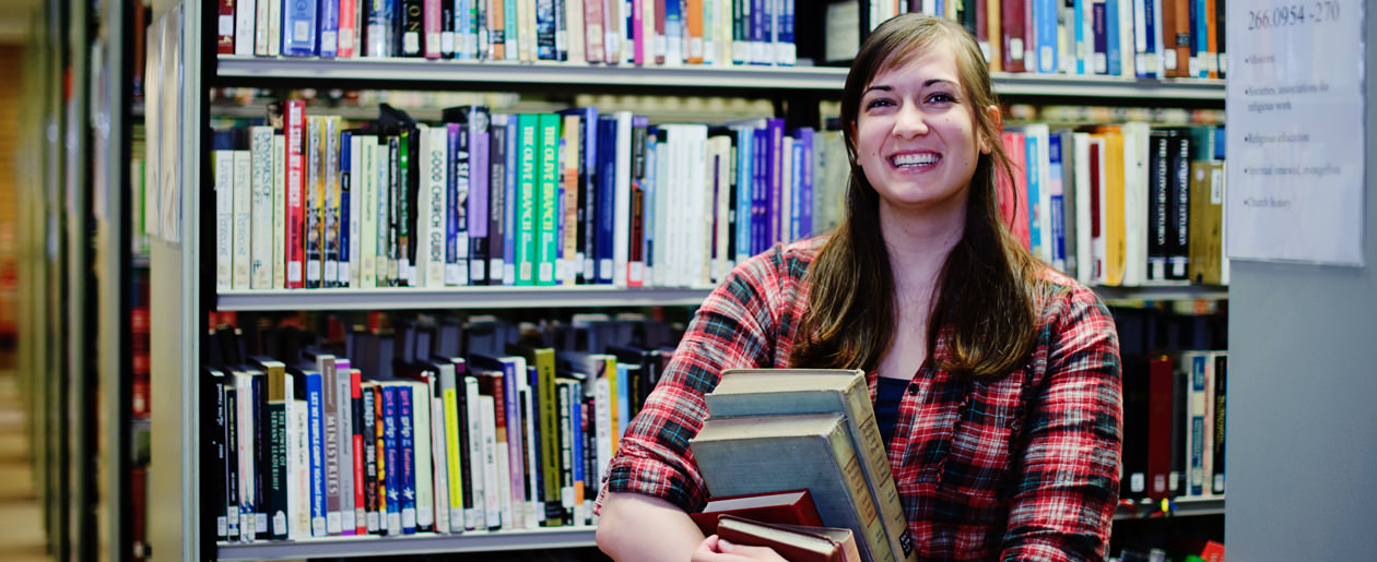 A young woman holds an armful of rare books from the Library