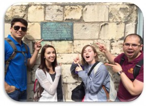 4 NTC foreign students pointing at a wall