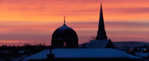 The Sun is setting behind a Mosque during an English winter. Snow lines the roofs nearby.
