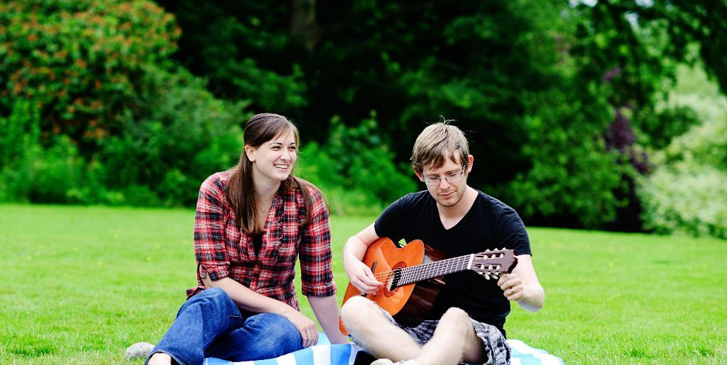 Two students sit on the grass while one tunes his guitar
